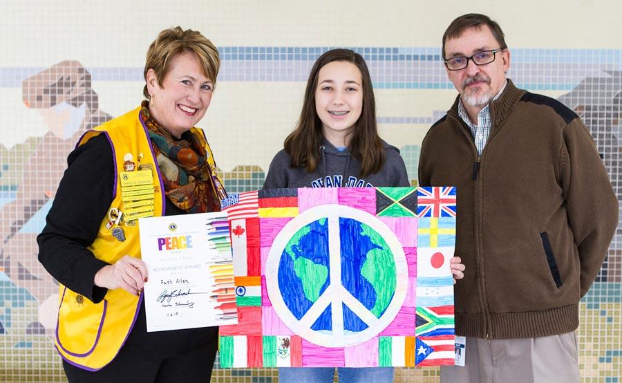 IMAGE: Lion Marilyn Carlson, Faith Allen and Phoenix Principal Hank Schmelz show off Allen's winning Peace Poster.